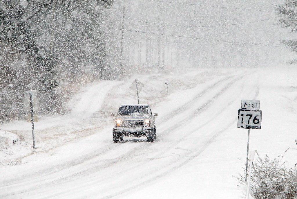 . A truck slowly travels on a snow covered Alabama highway 176  Tuesday Feb. 11,  2014 in Dog Town,  Ala. A winter storm dropped from 1 inch to 3 inches of wintry precipitation across a wide area, turning trees and roads white and forcing hundreds of schools, businesses and government offices to close or open late. (AP Photo/Hal Yeager)
