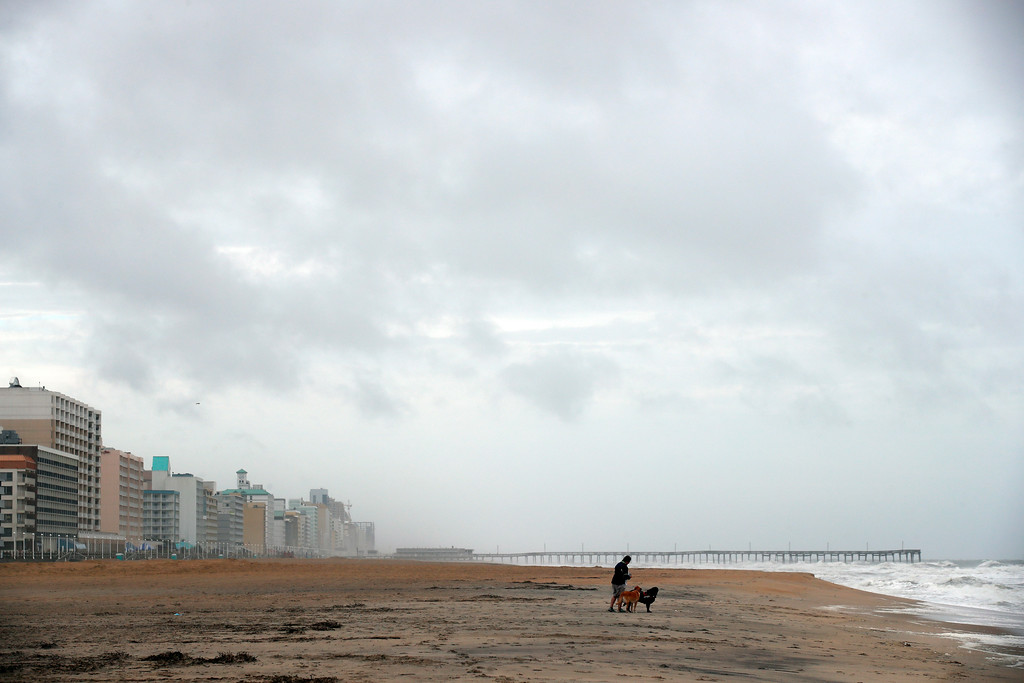 . Kelly McGuire walks her dogs Jack and Roxy on a mostly deserted oceanfront beach, Friday, Sept. 14, 2018, in Virginia Beach, Va., as the effects of Hurricane Florence are felt. (AP Photo/Alex Brandon)