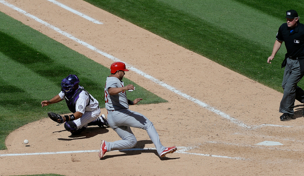 . St. Louis Cardinals shortstop Jhonny Peralta (27) scores on a sacrifice fly by St. Louis Cardinals right fielder Allen Craig (21) to Colorado Rockies center fielder Charlie Blackmon (19)  in the ninth inning June 25, 2014 at Coors Field. (Photo by John Leyba/The Denver Post)