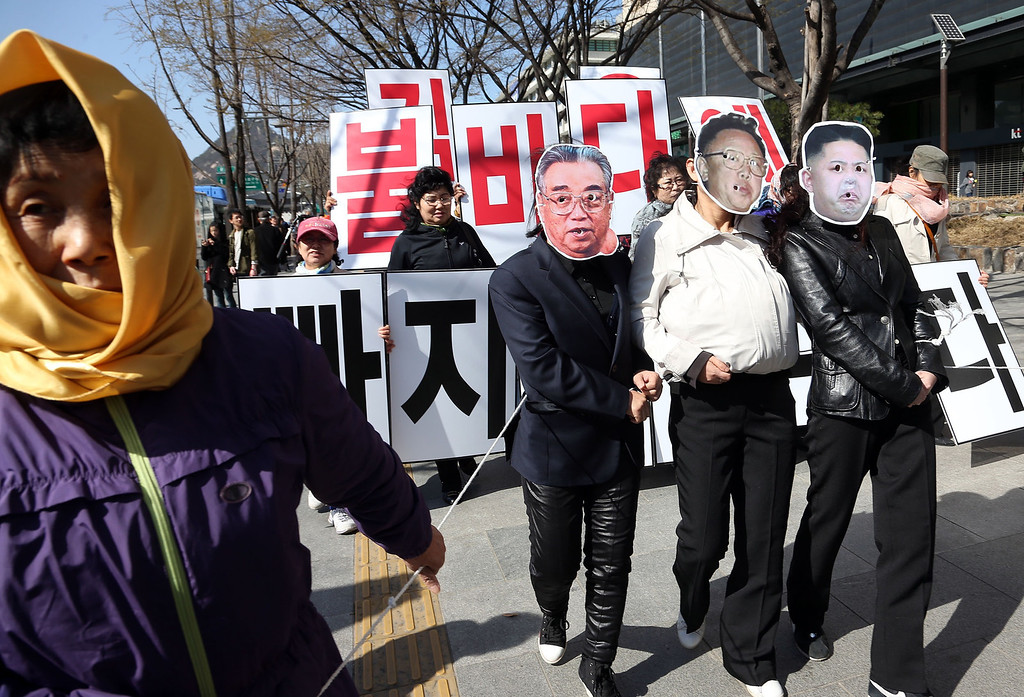 ". Activists wear masks resembling (L-R) late North Korean founder Kim Il-Sung, late leader Kim Jong-Il and current leader Kim Jong-Un during an anti-North Korea protest held by a civic group which consists of former female North Korean defectors living in the South, in Seoul April 14, 2013. Kim Il-Sung\'s 101st birthday falls on April 15, 2013. Korean characters in background read,""Kim Jong-Un, it is you who will fall into the sea of fire\"".          REUTERS/Lee Ji-Eun/Yonhap"