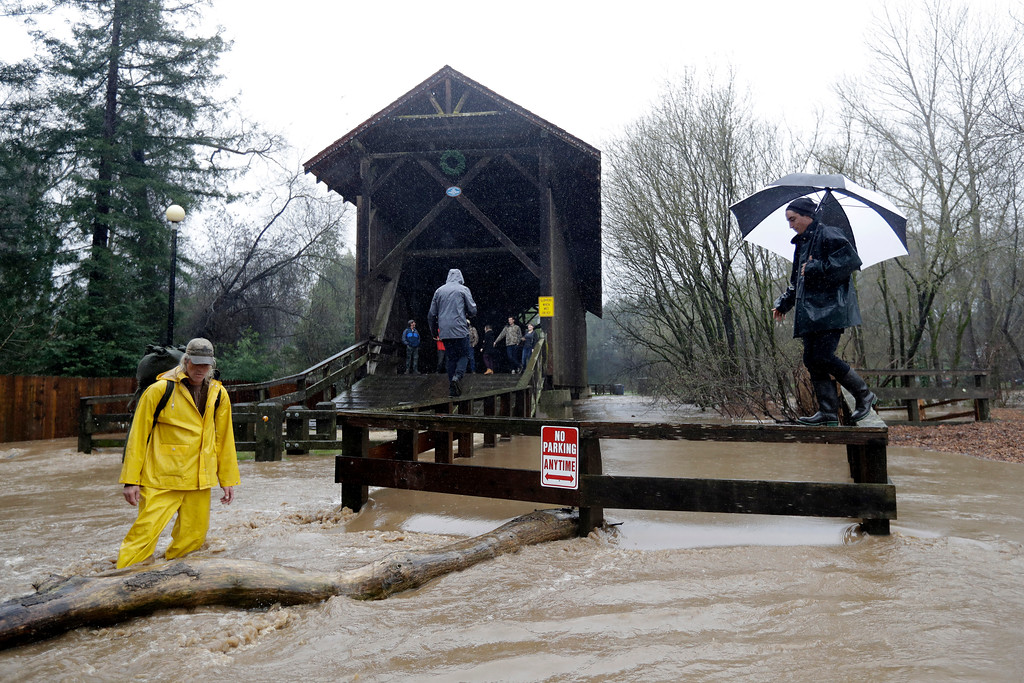 . People use a railing to access a covered bridge over the San Lorenzo River Tuesday, Feb. 7, 2017, in Felton, Calif. Flash flood watches are in place for parts of Northern California down through the Central Coast as heavy rains swamp roads and threaten to overtop rivers and creeks. (AP Photo/Marcio Jose Sanchez)