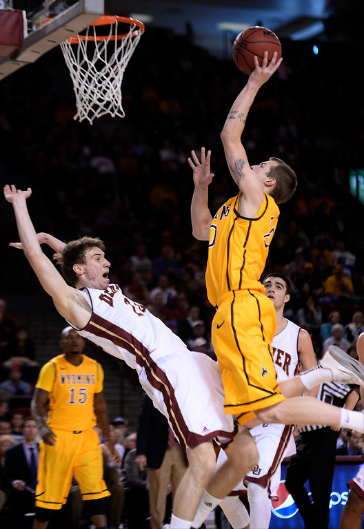 . Denver Pioneers forward Dom Samac (24) gets called for a foul as Wyoming Cowboys guard Nathan Sobey (20) drives to the basket during the first half December 15, 2013 Magness Arena. (Photo by John Leyba/The Denver Post)