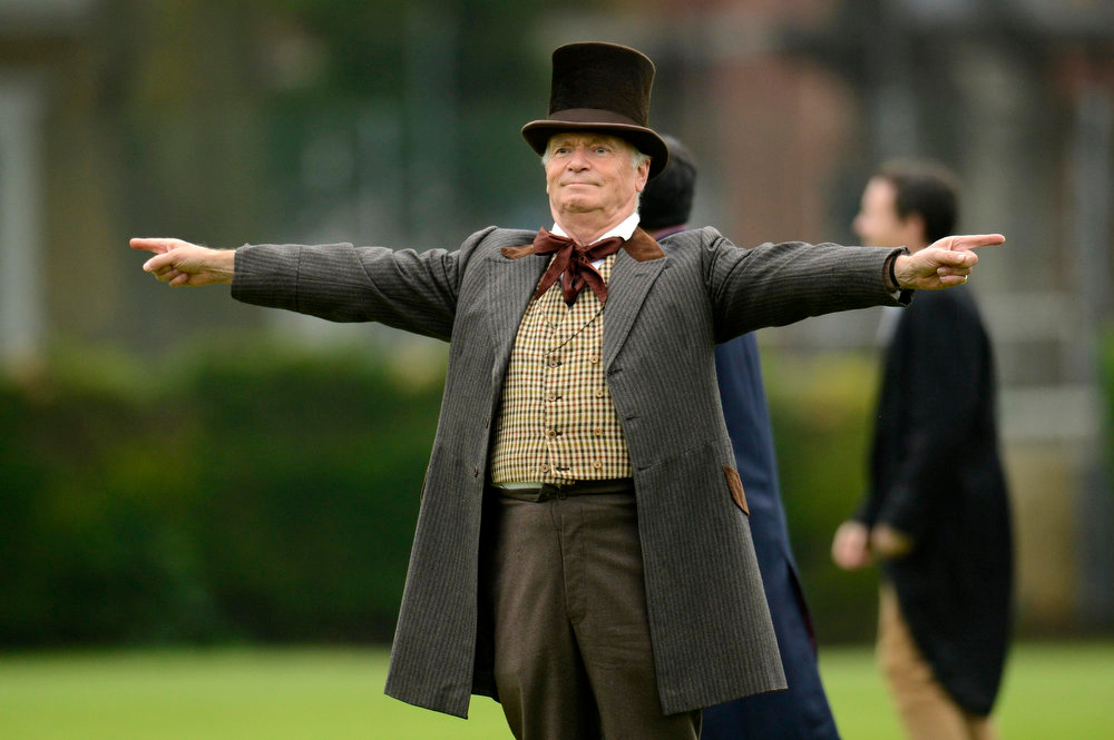 . Author Jeffrey Archer gestures as he acts as an umpire during a Victorian Cricket match to commemorate the 150th anniversary of Wisden Cricketers\' Almanack  at Vincent Square in London May 29, 2013. REUTERS/Philip Brown