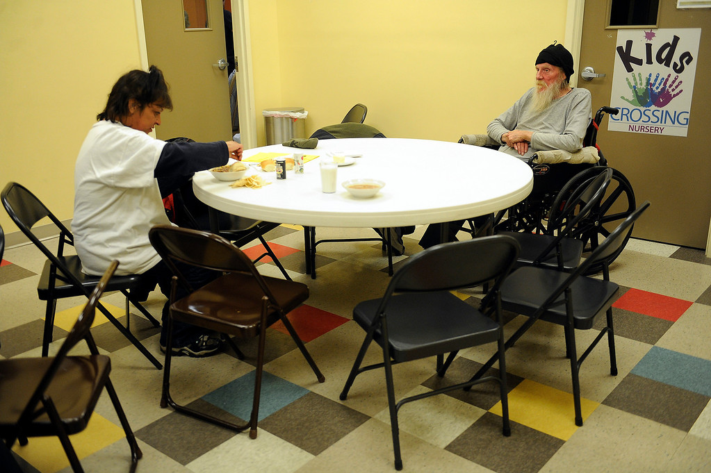 . WESTMINSTER, CO - JANUARY 22: Julie Clark, and Moon, no last name, eat dinner in the lunchroom at Applewood Community Church in Golden, Colorado on January 22, 2014. The Jefferson County Action Center began partnering with churches last year to offer emergency shelter for the homeless on severe weather nights. (Photo by Seth McConnell/The Denver Post)