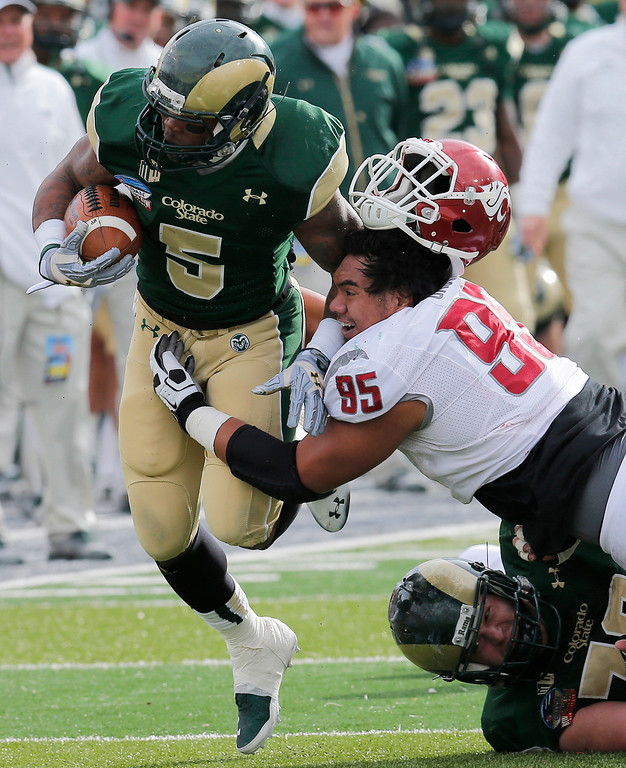 . Washington State nose tackle Ioane Gauta (95) loses his helmet as he hits Colorado State running back Kapri Bibbs (5) during the first half of the New Mexico Bowl NCAA college football game, Saturday, Dec. 21, 2013, in Albuquerque, N.M. (AP Photo/Matt York)