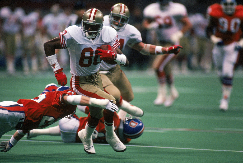 . Wide receiver Jerry Rice #80 of the San Francisco 49ers tries to outrun a diving tackle attempt by Denver Broncos defensive back Kip Corrington #25 during a game in Super Bowl XXIV at Louisiana Superdome on January 28, 1990 in New Orleans, Louisiana Photo by George Rose/Getty Images)