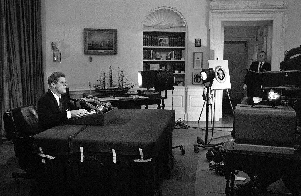 """. In this Oct. 22, 1962 file photo, U.S. President John F. Kennedy addresses the nation by television and radio from the Oval Office in Washington, announcing a U.S. naval blockade of Cuba. The Kennedy image, the \""""mystique\"""" that attracts tourists and historians alike, did not begin with his presidency and is in no danger of ending 50 years after his death. Its journey has been uneven, but resilient _ a young and still-evolving politician whose name was sanctified by his assassination, upended by discoveries of womanizing, hidden health problems and political intrigue, and forgiven in numerous polls that place JFK among the most beloved of former presidents.(AP Photo/WOA)"""
