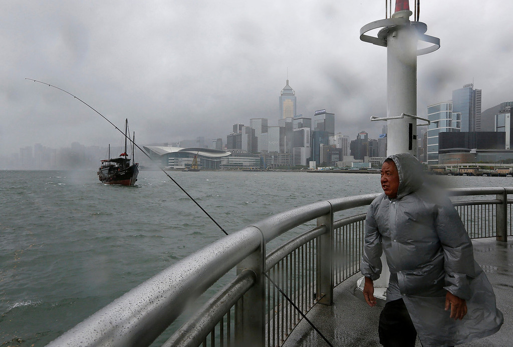 . A man battles against a strong wind as he throws a line at Hong Kong\'s Victoria Habour Tuesday, Aug. 13, 2013. The Observatory said Typhoon Utor intensified slightly as it moves towards the western coast of Guangdong. The typhoon battered the northern Philippines on Monday, toppling power lines and dumping heavy rain across cities and food-growing plains. The storm left at least two people dead and 44 missing. (AP Photo/Vincent Yu)