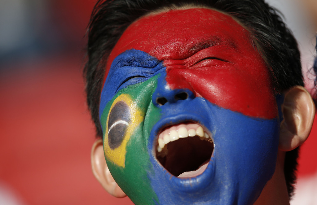 . A South Korea fan with his face painted in the colors of his country and of Brazil cheers prior to a Group H football match between South Korea and Algeria at the Beira-Rio Stadium in Porto Alegre during the 2014 FIFA World Cup on June 22, 2014.     ADRIAN DENNIS/AFP/Getty Images