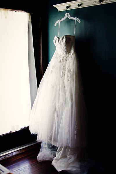 wedding gown hanging by window