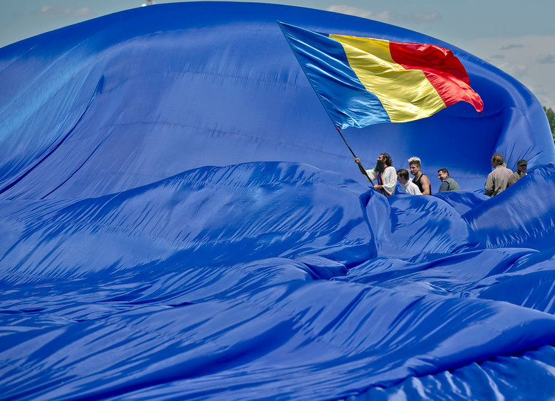 . Romanians struggle to control a huge national flag during a gust of wind on the Clinceni Airfield, south of Bucharest, Romania, Monday, May 27, 2013. Romania entered the Guinness Book of records after it unveiled the largest flag ever made. It took about 200 people several hours Monday to unfurl a five-ton flag of Romania which organizers said measured 349.4 meters by 226.9 meters, about three times the size of a football pitch.(AP Photo/Vadim Ghirda)