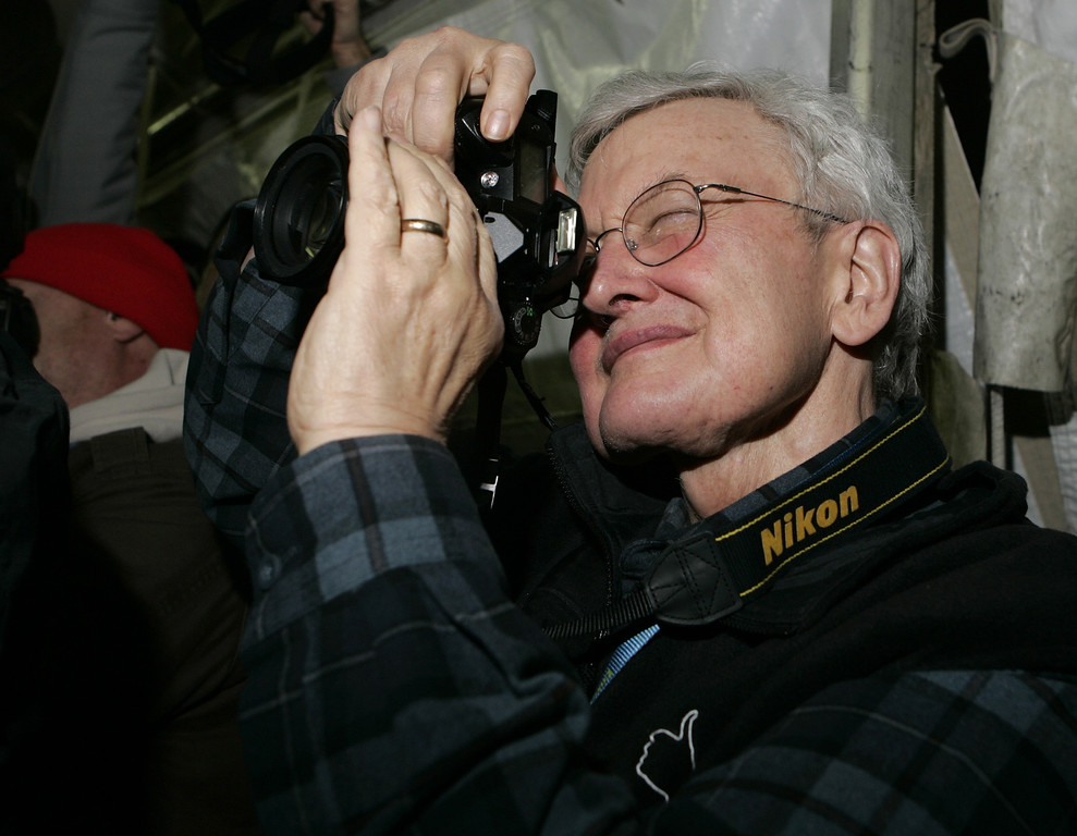 """. Movie critic Roger Ebert  photographs \""""The Darwin Awards\"""" director Finn Taylor from the media line before the the screening of the film during the Sundance Film Festival in Park City, Utah, Wednesday, Jan. 25, 2006. (AP Photo/Carolyn Kaster)"""