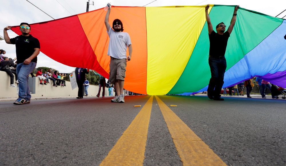 Description of . A group carries a rainbow flag as they take part in a march honoring Martin Luther King Jr., Monday, Jan. 21, 2013, in San Antonio. The nation honors civil rights leader Martin Luther King Jr. on Monday, the same day as it celebrates the inauguration of the first black president to his second term. (AP Photo/Eric Gay)