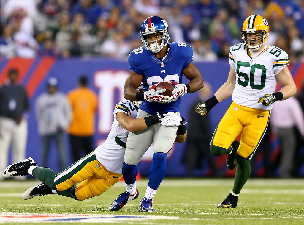 . Victor Cruz #80 of the New York Giants is tackled by  Micah Hyde #33 of the Green Bay Packers at MetLife Stadium on November 17, 2013 in East Rutherford, New Jersey.  (Photo by Elsa/Getty Images)