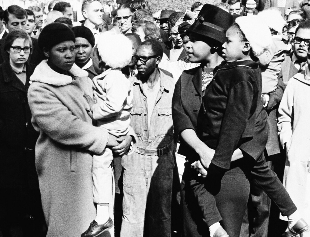 . Outside the Palace of Justice, Winnie Mandela (right) waits for a glimpse of her husband, Nelson Mandela , as he and seven other men are carried off to jail in Blacn Marias on June 12, 1964 in Pretoria, South Africa. The men had been convicted of sabotage and sentenced to life imprisonment. Mrs. Mandela waited in vain  the police van took another route and did not pass her. (AP Photo/ARG)
