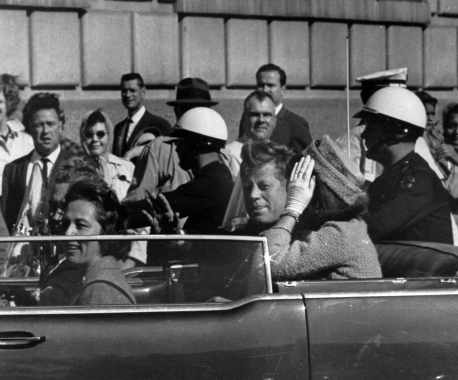 . President John F. Kennedy is seen riding in motorcade approximately one minute before he was shot in Dallas, Tx., on Nov. 22, 1963.  In the car riding with Kennedy are Mrs. Jacqueline Kennedy, right, Nellie Connally, left, and her husband, Gov. John Connally of Texas.  (AP Photo)