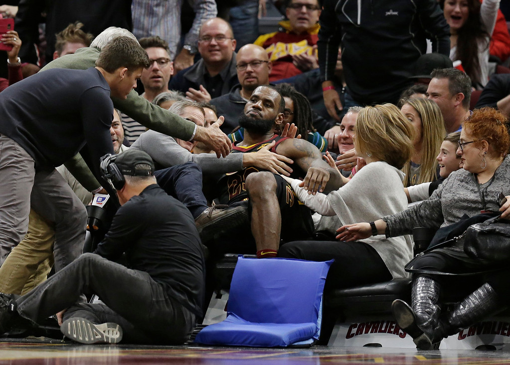 . Cleveland Cavaliers\' LeBron James (23) falls into the seats in the second half of an NBA basketball game against the Los Angeles Lakers, Thursday, Dec. 14, 2017, in Cleveland. (AP Photo/Tony Dejak)