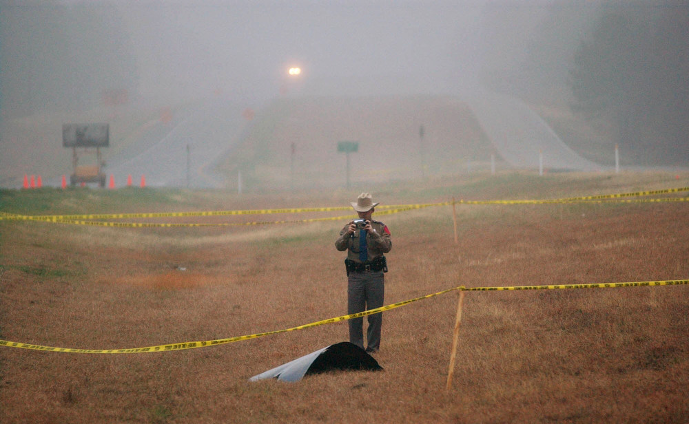 . A Texas Department of Safety trooper photographs part of what is believed to be a piece of debris from the space shuttle Columbia  along State Highway 155, north of Palestine, Texas, Sunday, Feb. 2, 2003. The shuttle tore to pieces Saturday 39 miles above Texas, killing all seven astronauts, in the last 16 minutes of a 16-day mission, as the spaceship re-entered Earth\'s atmosphere.  (AP Photo/San Antonio Express-News, Jerry Lara)