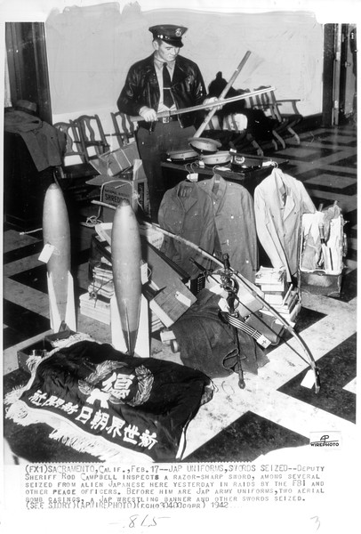 """""""Deputy Sheriff Rod Campbell of Sacramento inspects a razor sharp sword among several seized from Japanese there.  Before him are Jap army uniforms, two aerial bomb casings, a wrestlying banner and other articles taken by the FBI.""""--caption on photograph"""