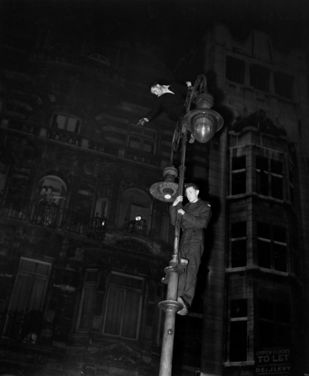 . Two men climb a lamppost during nighttime VE Day celebrations in the West End of London, England, on May 7, 1945.  (AP Photo)