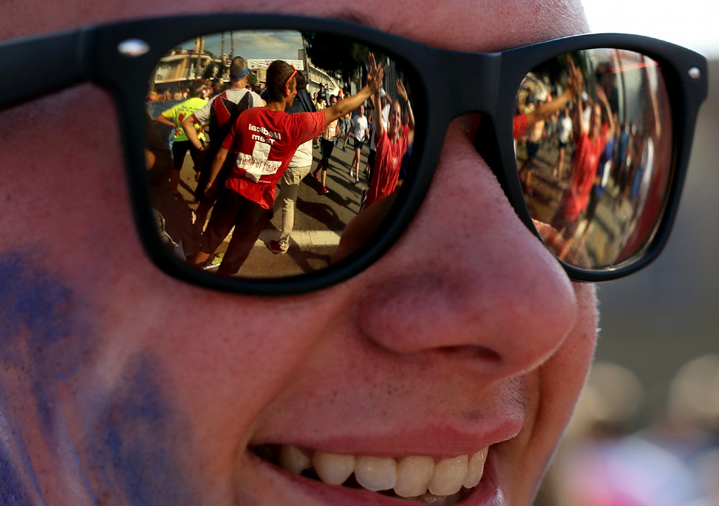 . Runners seen through a reflection in a man\'s glasses are greeted with high-fives as they finish the 42nd annual Wharf to Wharf race in Capitola on Sunday. (Kevin Johnson -- Santa Cruz Sentinel)