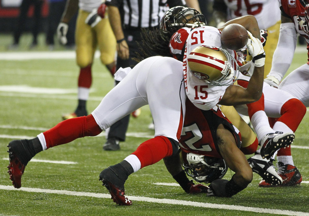 . San Francisco 49ers wide receiver Michael Crabtree (15) fumbles the ball as he is stopped on the goal line by Atlanta Falcons strong safety William Moore (L) and cornerback Dunta Robinson during the third quarter in the NFL NFC Championship football game in Atlanta, Georgia January 20, 2013. REUTERS/Gary Hershorn
