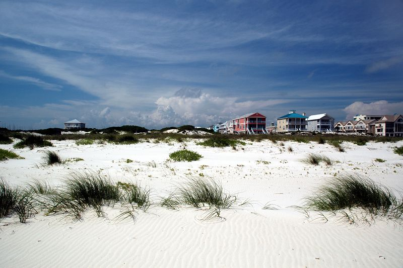 Another view of the beach, cottages, and clouds.