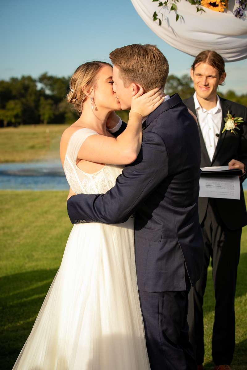 bride and groom's first kiss as husband and wife at the altar during their wedding ceremony