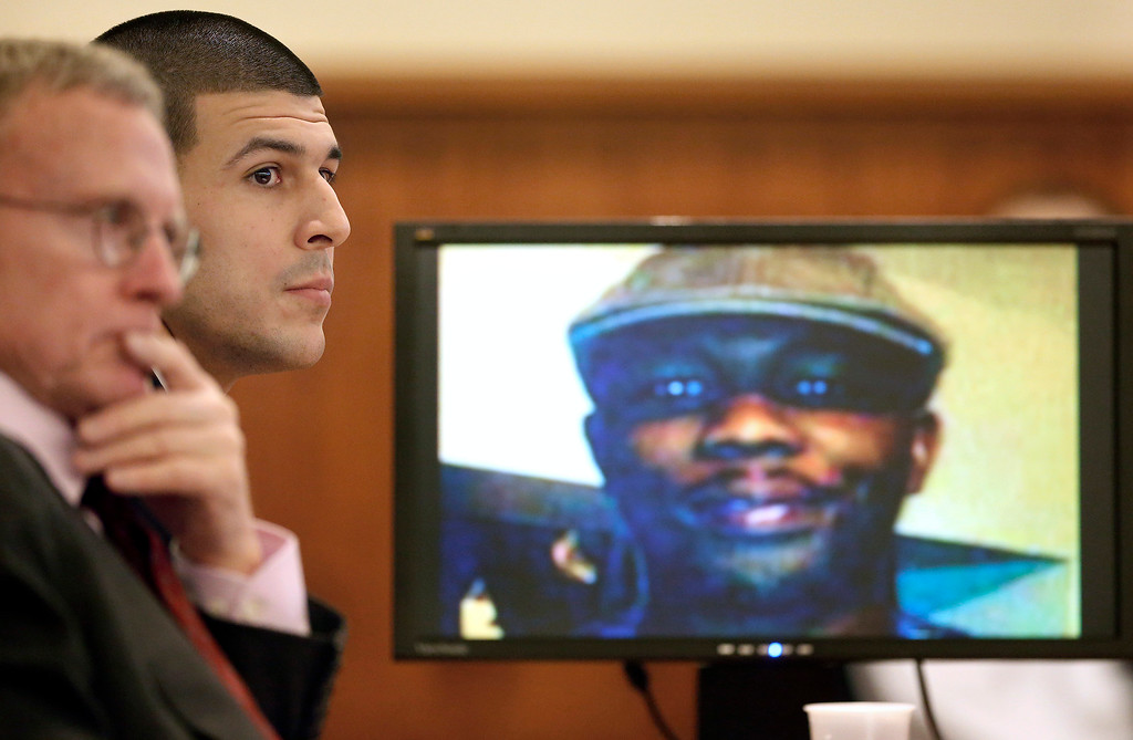 . Former New England Patriots football player Aaron Hernandez, center, listens during his murder trial, Thursday, Jan. 29, 2015, in Fall River, Mass., as defense attorney Charles Rankin, left, looks on while an image of Odin Lloyd is displayed on a monitor, right. Hernandez is charged with killing Lloyd, 27, a semiprofessional football player, in June 2013.  (AP Photo/Steven Senne, Pool)