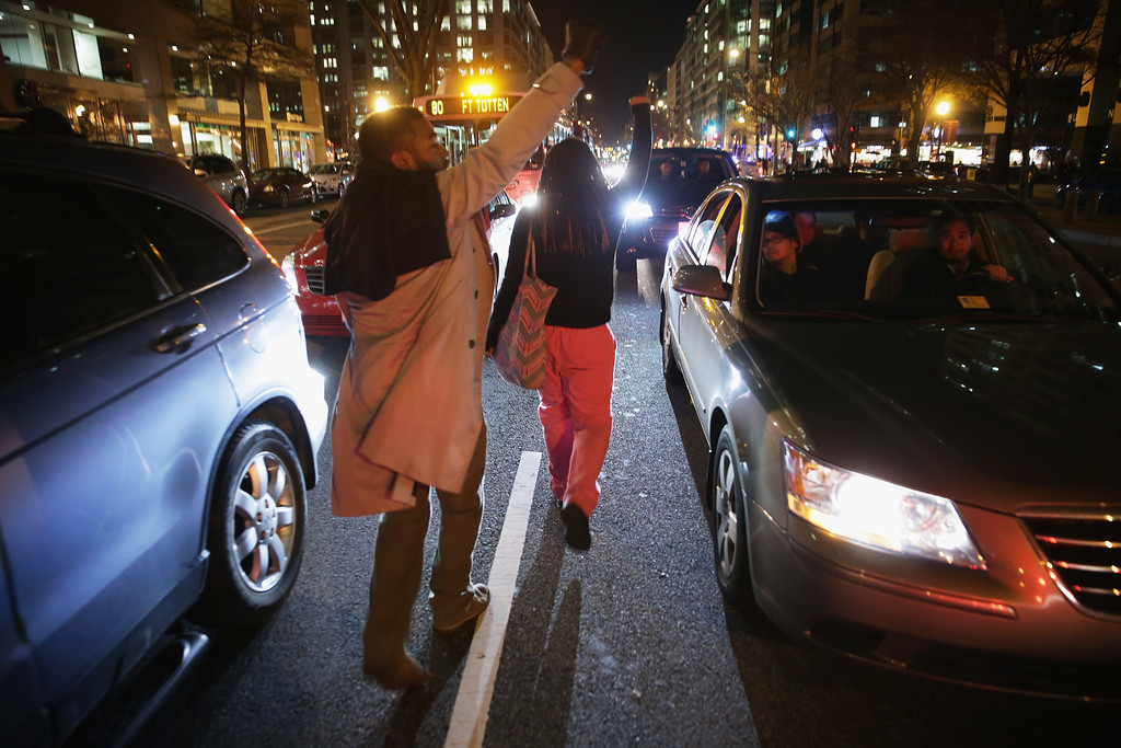 . WASHINGTON, DC - DECEMBER 03:  Demonstrators march through traffic during a protest against a New York grand jury decision December 3, 2014 in Washington, DC. The grand jury has decided not to indict police officer Daniel Pantaleo for the death of unarmed black man Eric Garner after putting him in a chokehold.  (Photo by Alex Wong/Getty Images)