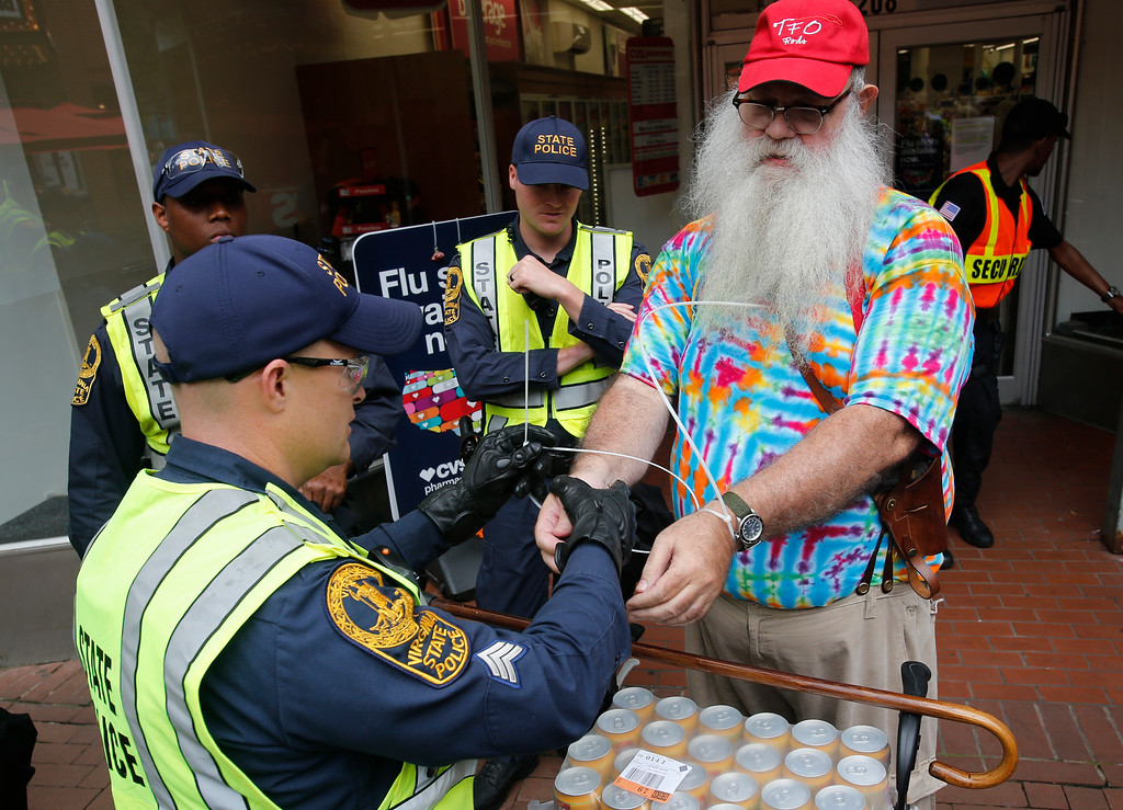 . State Police arrest a local resident, John Miska, in the locked down downtown area in Charlottesville, Va., Saturday, Aug. 11, 2018.   Miska purchased razor blades, which are banned items, in a downtown drugstore. On the the anniversary of white supremacist violence, state and local authorities framed the weekend\'s heightened security as a necessary precaution. (AP Photo/Steve Helber)