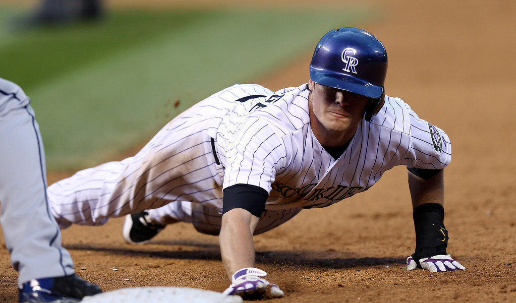 . Colorado Rockies\' Josh Rutledge dives back into first base on a pickoff attempt by the Atlanta Braves in the fifth inning of a baseball game in Denver on Wednesday, June 11, 2014. (AP Photo/David Zalubowski)