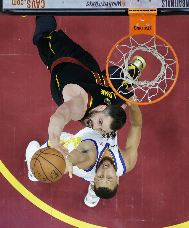. Golden State Warriors\' Stephen Curry and Cleveland Cavaliers\' Kevin Love, top, reach for a rebound during the first half of Game 3 of basketball\'s NBA Finals, Wednesday, June 6, 2018, in Cleveland. (AP Photo/Carlos Osorio, Pool)