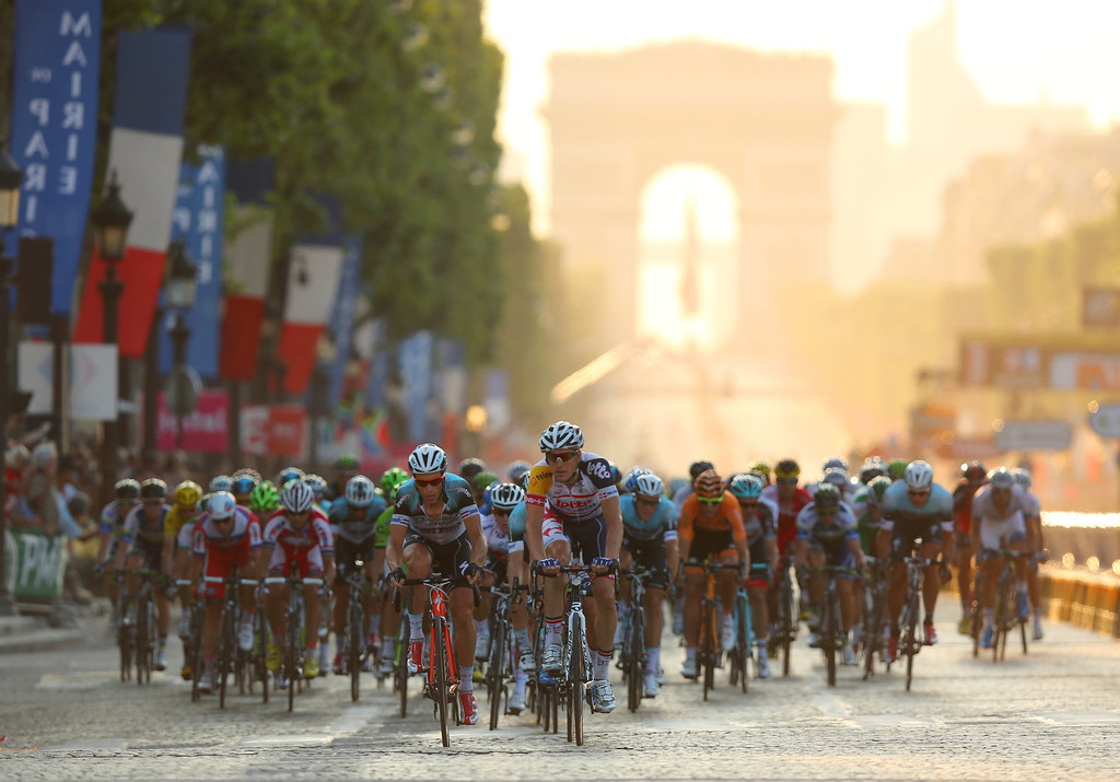 . The peloton carges away from the Arc d\'Triomphe during the twenty first and final stage of the 2013 Tour de France, a processional 133.5KM road stage ending in an evening race around the Champs-Elysees, on July 21, 2013 in Paris, France.  (Photo by Bryn Lennon/Getty Images)