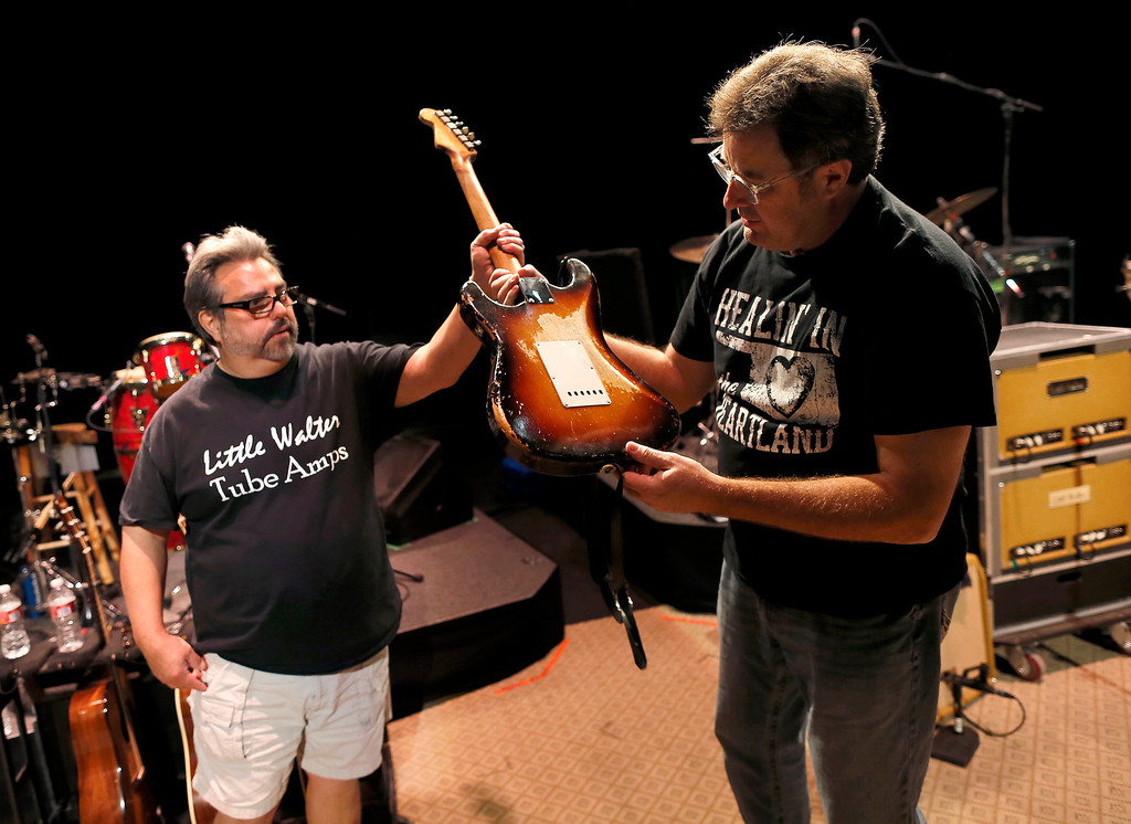 """. Guitar technician Vinnie Garcia hands Country legend Vince Gill his 1957 Fender Stratocaster after a sound check at the Mesa Performing Arts Center, in Mesa, Ariz. on Thursday, Oct. 24, 2013. Garcia, who has been best friends with Gill since the seventh grade, sold Gill his first Stratocaster for $200 and a pair of cowboy boots. Gill says, \""""I love the versatility of the guitar as much as anything, no matter what way you want to try to play it, it always responds.\"""" (AP Photo/Matt York)"""
