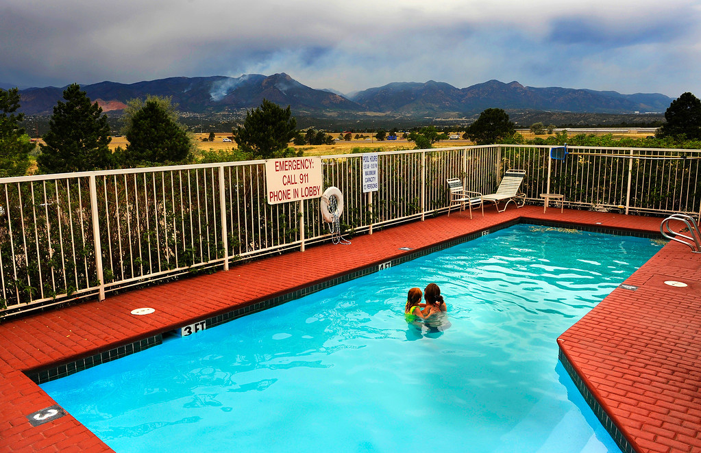 . Evacuees Alexandrea Hermes and her daughter, Ava, 5, watch as smoke rises from the mountains behind them, Thursday, June 28, 2012, as they swim in the pool at the hotel where they are now staying. Alexandrea\'s husband is on active duty, and the family lives on base at the Air Force Academy. They were forced to evacuate their home, which was in the path of the Waldo Canyon Fire in Colorado Springs, Colo.