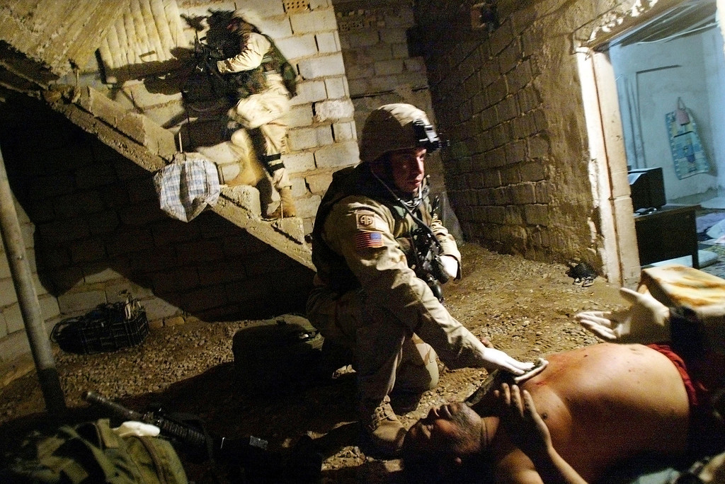 """. U.S. Army combat medic Sgt. Luis Pacheco of the 1st Brigade, 505th Parachute Infantry Regiment of the 82nd Airborne Division, from Chicago, Illinois, treats an Iraqi \""""insurgent\"""" for a gunshot wound to the chest as another soldier searches the home during early morning raids January 6, 2004 in Fallujah, Iraq. The Army said the man was fired upon by U.S. soldiers after brandishing a rifle. The raids netted four suspects including an Iraqi man suspected of constructing IED\'s for insurgents. (Photo by Mario Tama/Getty Images)"""