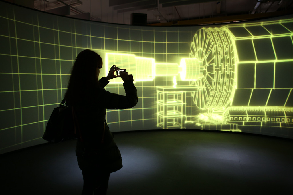 . A visitor to the Science Museum takes a phone photograph of a video projection showing the workings of the Large Hadron Collider (LHC)  at the \'Collider\' exhibition on November 12, 2013 in London, England.  (Photo by Peter Macdiarmid/Getty Images)