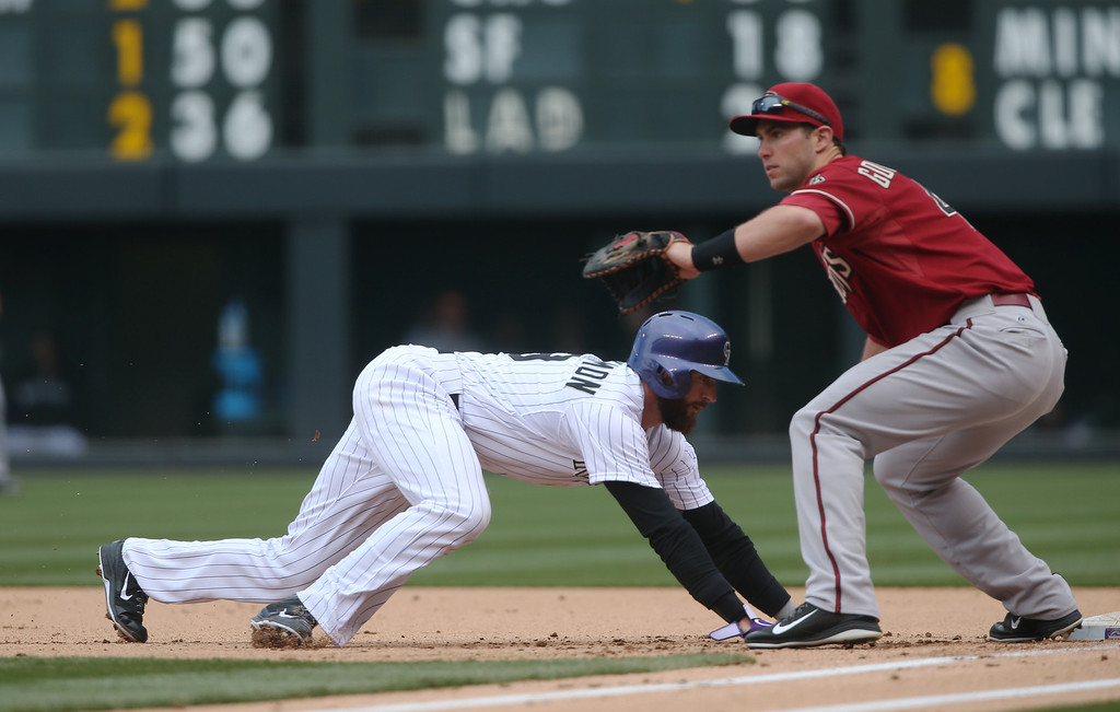 . Arizona Diamondbacks first baseman Paul Goldschmidt, right, fields pickoff throw as Colorado Rockies\' Charlie Blackmon scrambles back to first base in the first inning of a baseball game in Denver on Sunday, April 6, 2014. (AP Photo/David Zalubowski)