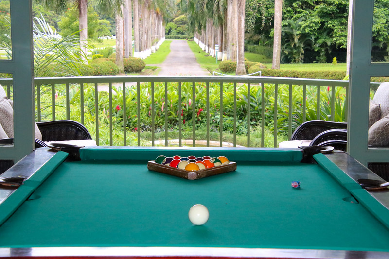 billiard table with balls and cue on table