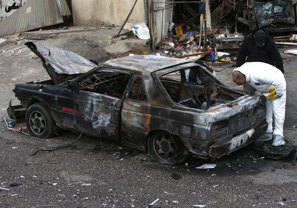 . A Lebanese police inspector, investigates the site of a deadly car bomb that exploded Saturday evening near a gas station, in the predominately Shiite town of Hermel, about 10 miles (16 kilometers) from the Syrian border in northeast Lebanon, Sunday, Feb. 2, 2014. (AP Photo/Hussein Malla)