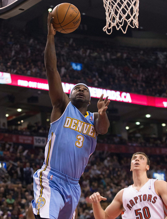 . Denver Nuggets\' Ty Lawson, left, goes up for a basket as Toronto Raptors\' Tyler Hansbrough looks on during first half of an NBA basketball game on Sunday, Dec. 1, 2013, in Toronto. (AP Photo/The Canadian Press, Chris Young)