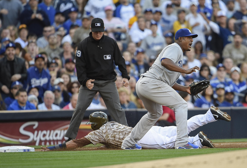 . Everth Cabrera #2 of the San Diego Padres slides safely into third base as Juan Uribe #5 of the Los Angeles Dodgers waits for the throw during the second inning of a baseball game on Opening Night at Petco Park on March 30, 2014 in San Diego, California.  (Photo by Denis Poroy/Getty Images)