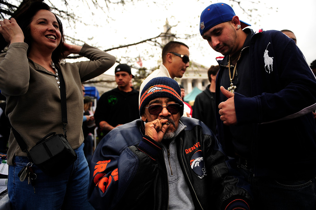 ". 65 year old Raul ""Padu\"" Hernandez of Denver hits a joint he is sharing with his friend Lorenzo Ortega at the Annual Denver 420 Rally in Civic Center Park.      Joe Amon, The Denver Post"