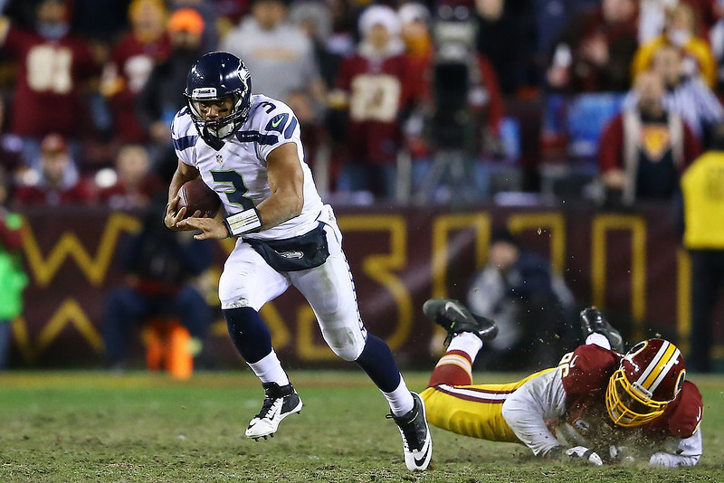 . Russell Wilson #3 of the Seattle Seahawks runs the ball against the defense of Barry Cofield #96 of the Washington Redskins in the second half during the NFC Wild Card Playoff Game at FedExField on January 6, 2013 in Landover, Maryland.  (Photo by Al Bello/Getty Images)