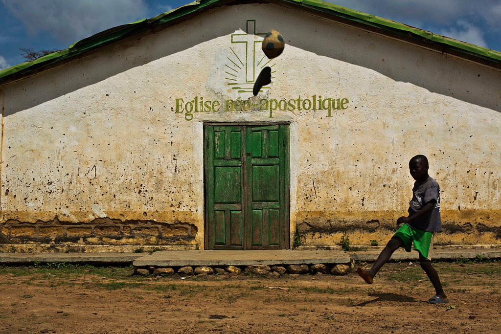 . In this photo taken Saturday Nov. 22, 2014, a young boy loses his shoe while kicking a ball in the Guinean village of Meliandou, some 400 miles (600 kms) south-east of Conakry, Guinea, believed to be Ebola\'s ground zero. (AP Photo/Jerome Delay)