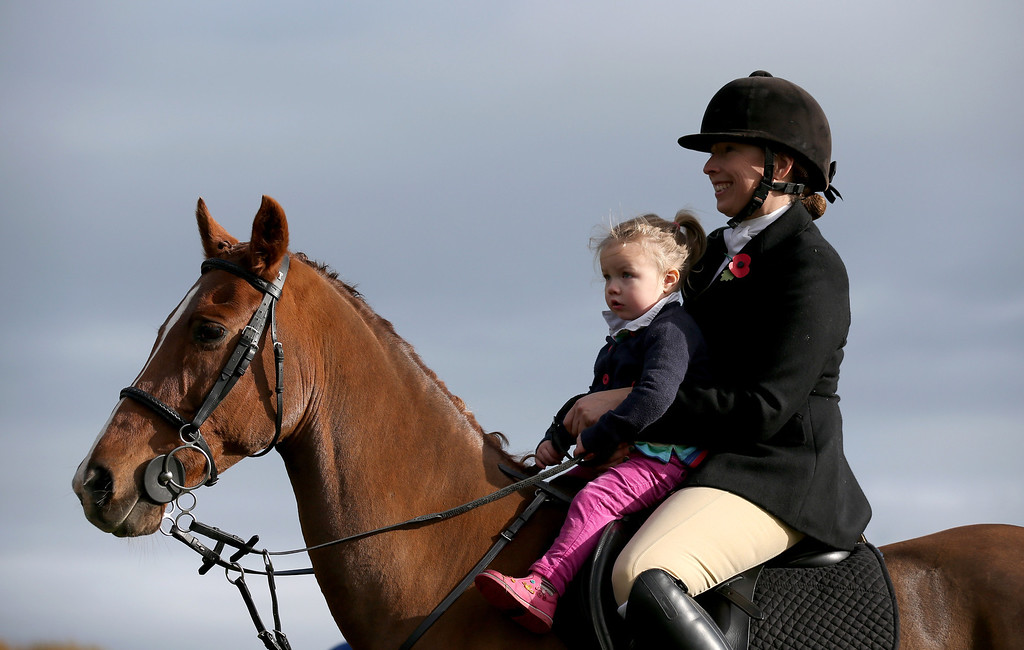 . BADMINTON, GLOUCESTERSHIRE - NOVEMBER 02:  A rider from the Duke of Beaufort\'s Hunt gives a ride to a young girl as they gather for the opening meet of the season at Worcester Lodge on November 2, 2013 near Badminton in Gloucestershire, England. Traditionally the hunting season starts at the beginning of November and although a ban on fox hunting with dogs has been in force since February 2005, many supporters of fox hunting are continuing to call for a repeal of the ban, saying the current law is hard to interpret and enforce.  (Photo by Matt Cardy/Getty Images)