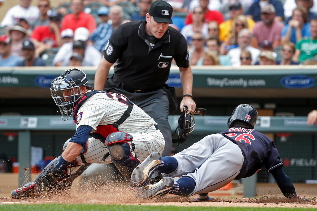 . Cleveland Indians Rajai Davis, right, slides ahead of the play by Minnesota Twins catcher Mitch Garver to steal home as umpire Chris Conroy watches in the sixth inning of a baseball game Wednesday, Aug. 1, 2018, in Minneapolis. (AP Photo/Bruce Kluckhohn)