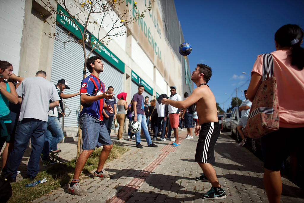. Argentine tourists play with a ball as they stand in line outside Independencia Stadium for free tickets to watch a practice session by Argentina\'s soccer team in Belo Horizonte, Brazil, Tuesday, June 10, 2014. The World Cup starts on June 12. (AP Photo/Victor R. Caivano)