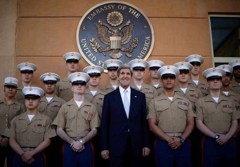 . U.S. Secretary of State John Kerry (C) poses for a picture with U.S. Marines based in Baghdad during his visit to the U.S. Embassy in Baghdad March 24, 2013. Kerry made an unannounced visit to Iraq on Sunday and said he told Prime Minister Nuri al-Maliki of his concern about Iranian flights over Iraq carrying arms to Syria.   REUTERS/Jason Reed